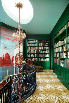 Emerald green bookshelves, skylight, interesting rose gold light fixture, what appears to be leopard carpet...yes.