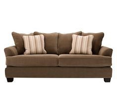 """This kathy ireland Home Ryann microfiber sofa not only encourages you to stay in your """"comfort zone,"""" it will help you create it! Its stain-fighting, cappuccino-colored microfiber upholstery is soft to the touch, while the tailoring and low-style seating are just what today's contemporary decorators are looking for. Pretty, tonal striped pillows elevate the look."""