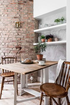 Kitchen table with vintage chairs, exposed brick and built-in shelves