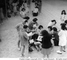 Students signing each other's 1945 yearbooks :: Topaz Museum