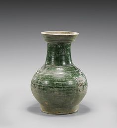 """HAN DYNASTY GREEN GLAZED POTTERY HU vase; the bulbous body with ridging and two moulded mask and faux-ring handles; with allover moss-green glaze H: 14""""; Hong Kong Art Craft Merchants Association certificate of antiquity."""