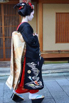 Maiko. Love her beautiful golden obi, black kimono, and red hair decorations. I think that she will make a great geisha <3