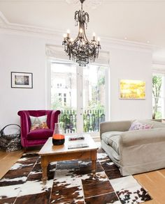 Eclectic London living room - love the berry purple chair and patchwork cowhide rug,