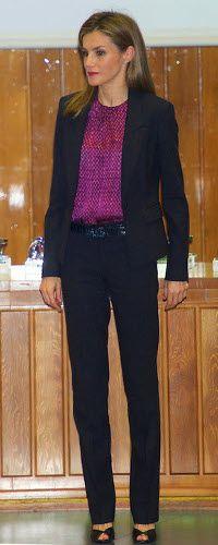 Como suele ser habitual en este tipo de eventos, doña Letizia ha apostado por su traje oscuro de Hugo Boss, cinturón de piel a juego y peeptoes negros, pero ha roto la monocromía con una llamativa blusa con estampado geométrico en color fucsia.