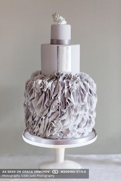 dove grey ruffle wedding cake topped with silver crown