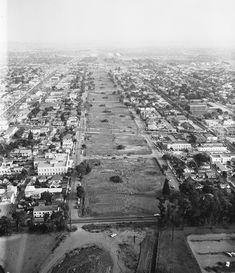 A residential strip demolished to build the 405 Freeway. This 1957 view is to the south. The two streets paralleling the demolition zone are Cotner on the left and Beloit on the right. The first foreground cross-street is Ohio, and the diagonal street two blocks south is a remarkably quiet Santa Monica Boulevard. The big white, two-story building at the lower left is Verizon today. It is painfully obvious from this picture how freeways permanently divide neighborhoods.