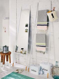 Escalera decorativa, que hace las veces de toallero y de la que cuelga una cestita para cepillos, y un espejo de pie con repisa. Escalera, espejo, taburete, cestas y cajas metálicas, en Car Möbel.
