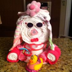 Girl Dog Diaper Cake: - 30 Pampers Swaddlers, - 2 Washcloths, - 1 Baby  Bib, - 1 Baby Bottle, - 1 Baby Sunglasses, - 2 Baby Blankets, - 3 Baby Bows, - 2 Onesies,  - 1 Rattle, - 1 Duck, and Several Rubberbands