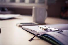 Auf einem Schreibtisch liegt ein Terminkalender mit einem Stift. Im Hintergrund…