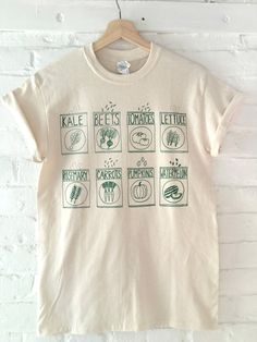 Hand Printed and Hand Drawn! This is a 100% cotton screen printed t shirt with packets of seeds-- pumpkins, herbs, zucchini, watermelon, beets, kale, carrots, lettuce and tomatoes. This shirt is perfect for gardeners! The shirt shown here is Natural and printed in green ink. // PROCESS: