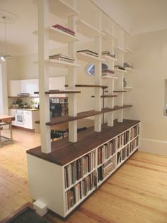 Belsize Shelving. This elegant room divide is also structural. Knocking through the two rooms meant having a very large supporting beam, however by making the uprights out of steel we used one a fraction of the size (and cost!). These uprights were clad with lacquered MDF that have a hidden adjustable peg system to make the shelves appear floating