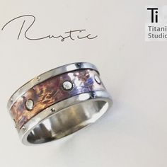 Titanium rustic and vintage designed ring. Titanium base with copper inlay and silver studs.