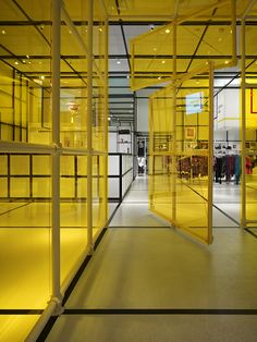 Uptown Kids by Elliott + Associates Architects. The store includes an airy, contemporary design that beautifully showcases the clothing and accessories. Store features a yellow plexiglass playroom so parents can keep an eye on their children enjoying some playtime.