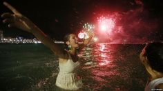 Revellers celebrate as fireworks explode during new year festivities on Copacabana Beach, Rio de Janeiro (two hours behind Greenwich)
