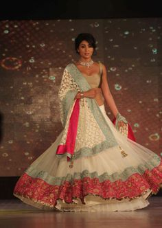 Zomg white lehenga with a gold blouse and bright colors for the border !