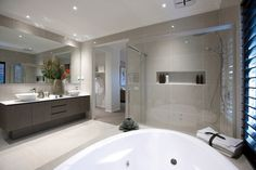 This double ensuite screams Balinese luxury. Space is created with a palette of light greys and white and functionality is achieved with recessed shelving and double shower heads.