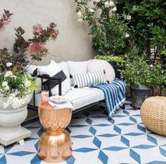 El jardín interior es una de las tendencias más fuertes esta temporada. Aquí decoraron esta terraza con un illón blanco, piso de pasta (mosaicos) en azul y blanco. Un otomán de rattan y macetas con flores dan el toque final.