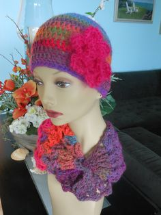 Hand crocheted wool hat and matching neck scarf - Vibrant orange and raspberry with blue and purple accenting colors. Fuzzy fuchsia flower accent - hand crocheted