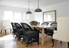 Modern cottage design with galvanized metal light pendants over light wood rectangular coffee table lined with black wicker chairs as well as cream wingback captain chairs.