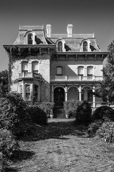 Black and white photograph of the front of Riverlore Mansion, a stately white home built in Cairo, Illinois in 1865 by a wealthy riverboat captain, who made his fortune on the two nearby rivers (the Ohio and Mississippi) that converge at Cairo. According to legend, the upper floor pilot's room was built to allow the captain to see the rivers from his home.