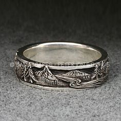 This is another landscape band in my series of the same. A band with some extremely detailed carving of mountain peaks, pine trees, and mountain streams. The picture does not repeat in any way as it goes around the finger. There are several different mountains, a couple meandering rivers, and groves of trees. The band has a formal polished border which frames the scenery. The scene itself is lightly polished, with the background oxidized to show the detail. The ring is 6mm wide; 2mm thick…
