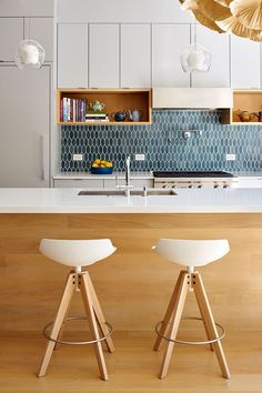 9 Inspirational Kitchens With Geometric Tiles // These blue hexagon tiles have been elongated to give the backsplash of this bright kitchen a unique touch.