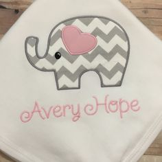 This is a wonderful gift set for any newborn or bundle of joy on the way.  White cotton bodysuit personalized with appliquéd love elephant. This set is sure to please any parent. Perfect gift for shower, baby arrival or take home hospital set. Keep it classy with trendy Love Set. Blanket measures approx. 36x26 and is 100% cotton. The beautiful Shabby Chic flower on beanie is supplied by www.BandsforBabes.Etsy.com. Bodysuit sizes available in both short sleeve (S/S) or long sleeve (L&#x2F...