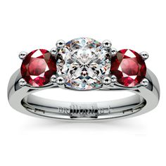 Trellis Three Ruby Gemstone Engagement Ring in Platinum Two perfectly matched round cut ruby gemstones are prong set in this platinum gemstone engagement ring setting, accenting your choice of center diamond. Proudly made in the USA.