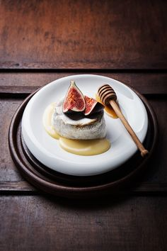 Baked Camembert with fresh figs and honey on a wooden background, closeup