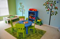 Garden playroom - Sky blue walls provide the backdrop for a mural of bright flowers, apple trees, and birds in flight. Painted furnishings in shades of sunny yellow render a cheerful atmosphere. Vivid wall stickers of butterflies peer down from the ceiling above and a string of flower-shaped lights festoon the window above the filmy blue curtains.