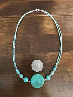 Beautiful statement coin turquoise necklace, centre piece 28mm round coin turquoise bead (4mm depth), necklace decorated with 7mm round beads with silver capstone silver findings and daisy rings,, 6mm smaller round beads, 10x3mm tube beads, double line of tiny Nepalese traditional beads