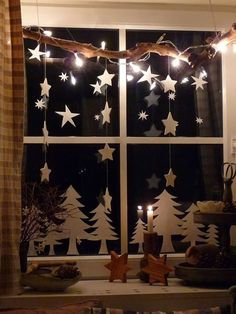Simple Christmas trees and stars hanging from a branch window display