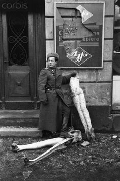 A Soviet soldier stands with broken mannequins and a shattered Agfa film sign in Berlin after the Soviet invasion at the end of World War II.