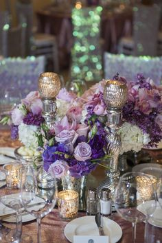 Pink and purple floral arrangements were arranged in urns and surrounded by mercury-glass candle holders and votives. #centerpiece Photography: Christine Bentley Photography. Read More: http://www.insideweddings.com/weddings/pastel-pink-purple-celebration-at-the-resort-at-pelican-hill/591/