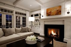 large fireplace and detail in the living room with nice windows and French doors.