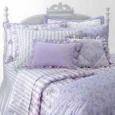 Lavender shabby chic bed linens and coordinating throw cushions. Perfect for a guest bedroom someday, as long as it's done tastefully!