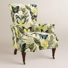 Featuring a classic silhouette in a butterfly and botanical print, our upholstered armchair adds chic sophistication to the living room or bedroom. Curvaceous dark walnut legs with metal casters complete its eye-catching appeal.