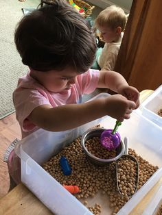 Sensory Play with Cherry Pits and a variety of scoops and bowls.