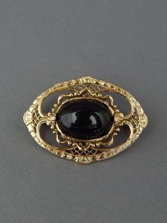 Vintage Black and Gold Round Filigree Brooch Pin, Gold Tone Black Cabochon Collar Brooch Neo Victorian, Estate Jewelry  ♥ Beautiful oval brooch in Victorian style featuring gold tone filigree and a black cabochon in the center  ♥ Secure roll-over pin in the back  ♥ Measures 1-5/8 x 1-1/8  ♥ Excellent condition. Please review the pictures.  ♥ A stunning piece of retro jewelry and a great gift!  Buy with confidence and enjoy