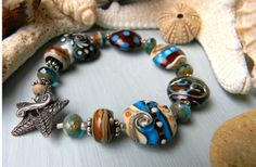 Where the Earth Meets the Sea  Artisan Lampwork Bracelet   By:  Fire-Imp Lampwork Beads  Inspired by rugged shorelines with pounding surf, craggy rocks, and tidepools swirling over starfish, urchins, and shells. A beachcombers delight, this bracelet combines rustic earthy colors with sandy beach colors and bright blue. Ornate and detailed, the handmade lampwork beads are accompanied by sterling silver beads, Czech glass, and a beautiful pewter starfish toggle clasp. One of a kind.  Bracelet…