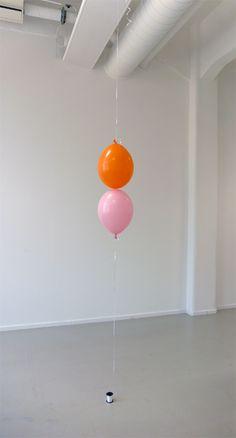Queda e ascensão. Um balão colorido (preenchido com uma respiração) suspenso do teto a partir de uma fita branca. Outro balão (cheio de hélio) fixo no chão flutuando em uma fita branca. Os dois balões suavemente se tocam na altura da cabeça (tomando um homem médio como referência).