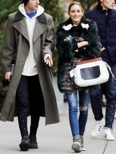 Olivia Palermo wears a multicolor fur coat, top-handle bag, skinny jeans, and high-top sneakers