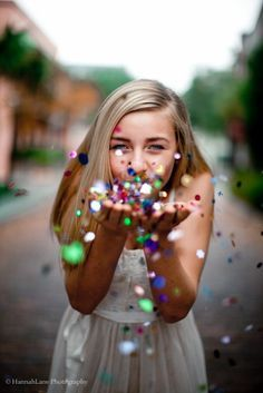 A girl blowing a handful of colorful shiny glitter at the camera