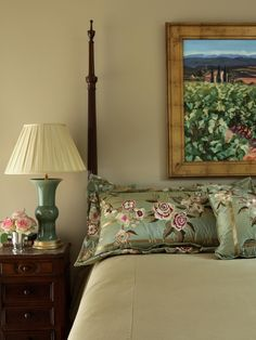 A small wood nightstand is used for a green table lamp and a small pink floral arrangement are positioned next to a four-poster bed, which has two blue and pink satin decorative pillows. A framed pastural painting hangs above the bed on taupe-colored wall,
