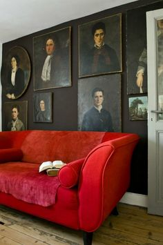 Old portraits in a dark, neutral palette on a matching painted wall.  That sofa pops.