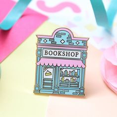 A beautiful and detailed bookshop enamel pin. Declare your love forbooks and reading with this cute pastel bookish pin, perfect for book lovers and readers! Jacket Pins, Cool Pins, Pin And Patches, Schmuck Design, Disney Pins, Up Girl, Pin Badges, Stickers, Lapel Pins