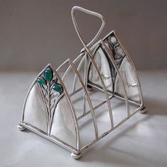This is not contemporary - image from a gallery of vintage and/or antique objects. C. R. ASHBEE (1863-1942) THE GUILD OF HANDICRAFT Ltd. (1888-1907) An Arts & Crafts silver toast rack set with green chalcedony.