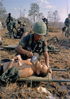 April 2, 1967 - A wounded US soldier is given water on a battlefield in Vietnam.
