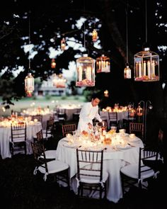 Cast a warm glow from above. A midsummer night's meal at an outdoor reception is served on the lawn under tall maple trees strung with lanterns hanging on chains from strong branches. Small and large, these lamps hold ivory tapers, their bases disappearing in a thick layer of fresh, fragrant rose petals.
