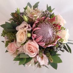 South African inspired blush pink bouquet. King protea, blushing bride protea, roses, brunia berries and mixed bush foliage. Surrey wedding flowers by Boutique Blooms floral design.